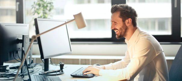 Mand sidder på kontor og er glad for noget